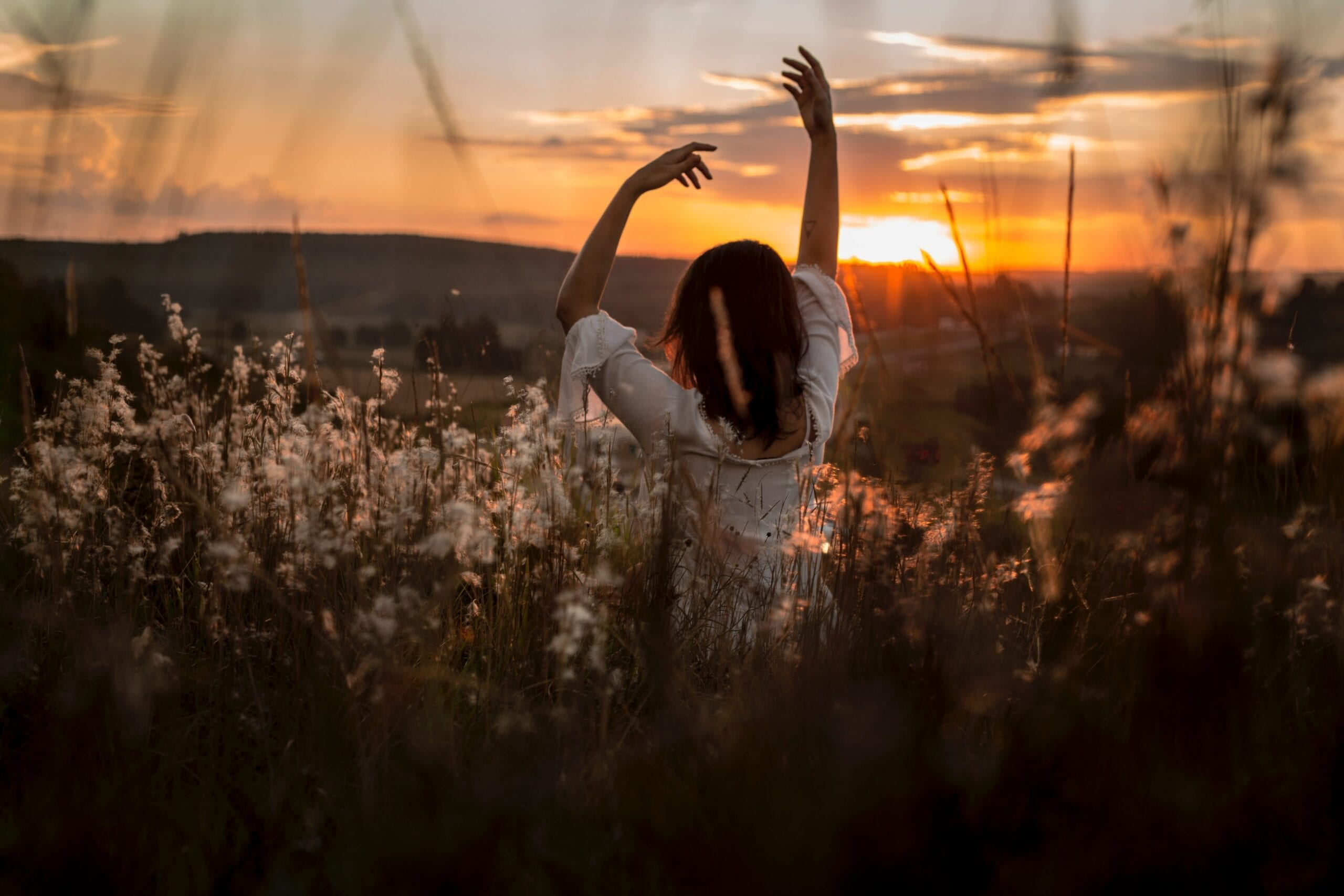 Lady dancing in grass watching the sunrise